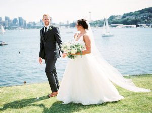 Bride and groom on Seattle waterfront on their wedding day | Photo by Alexandra Grace Photography | Wedding Planning by Perfectly Posh Events | Bouquet by Studio 3 Floral