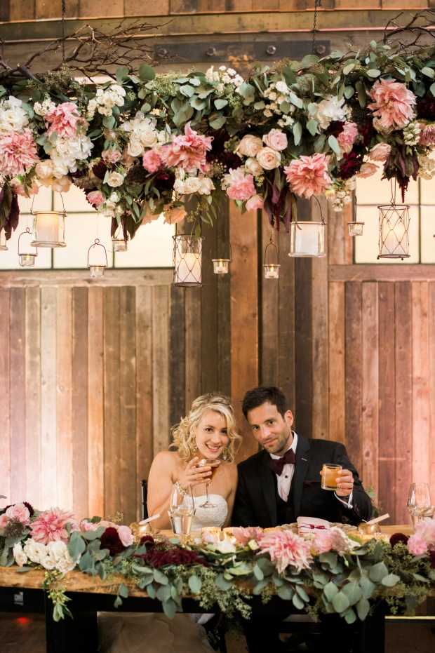 Sodo Park Wedding in Seattle | Bride and groom under suspended floral and branch installation as backdrop for sweetheart table | Perfectly Posh Events | Kimberly Kay Photography | Floressence