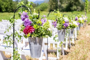 Galvanized buckets on shepherds hooks with lush green, purple, and pink florals as markers down ceremony aisle   Meadowbrook Farm Wedding, Snoqualmie, WA   Perfectly Posh Events, Seattle Wedding Planner   Down to Earth Flowers   Sasha Reiko Photography   Jesse + Wes Wedding // © Sasha Reiko Photography