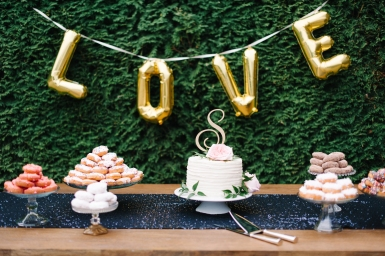 Wedding dessert display with LOVE gold balloons and donuts, seattle wedding planner Allison Dan Woodinville Wedding by Perfectly Posh Events, Photo by Blue Rose Photography