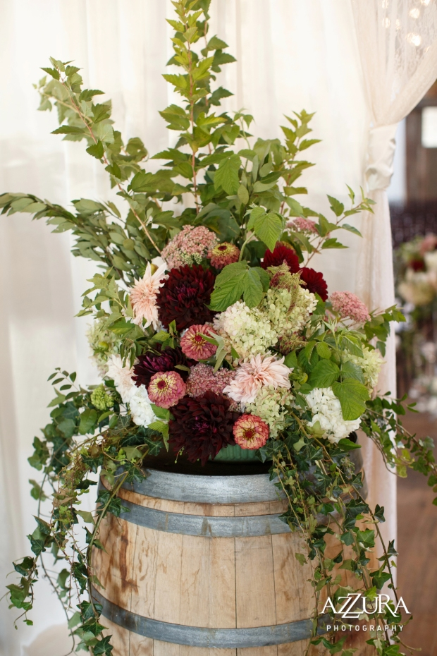 Sodo Park with Herban Feast Wedding in Seattle | Real Wedding use of Greenery, 2017 Pantone Color of the Year | Full, elegant arrangement with greenery, burgundy, pink, and cream florals on wine barrel | Perfectly Posh Events, Seattle Wedding Planning | Azzura Photography | Floral Design by Nova
