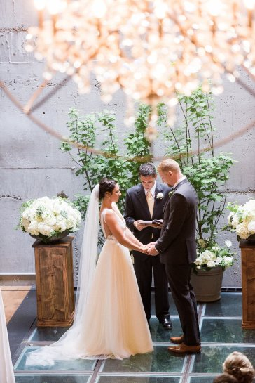 Makayla and Johnny's Wedding at Fremont Foundry in Seattle | Alexandra Grace Photography | Wedding Planning by Perfectly Posh Events, Seattle Wedding Planner | Wedding ceremony at Fremont Foundry with white flowers and green tree backdrop, urban chic wedding in Seattle